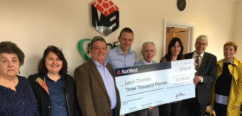 Martin-Brooks directors, John Elmore and Nick Brooks (third and fourth left), present local charity representatives with the proceeds from their latest fundraising efforts.