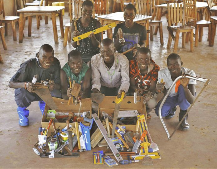 Some of the young people in Uganda who are supported by Amigos with tools that have previously been donated by RGB customers