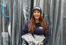 Rainclear's sales support administrator, Freya Cottell, wearing the winter hat and fleece, and holding an example of fittings customers can expect to receive for free with orders placed in January